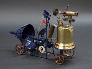 """a behind angle of the metal sculpture known as """"Fiery Sprinter"""" a small metalwork vehicle adorned with the number 9 and made to appear as though rocket powered"""