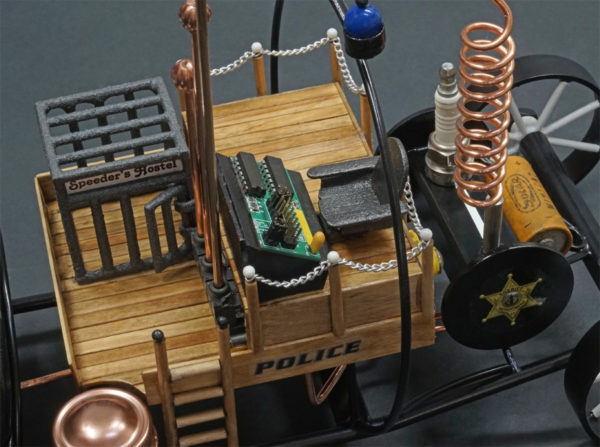 """the metalwork and wood sculpture """"Speeder's Chagrin"""" a retro futuristic depiction of a police vehicle making use of a camera, spark plugs and micro controller boards in it's construction. the words POLICE and LAW ENFORCEMENT can be seen on the sides and overhang"""