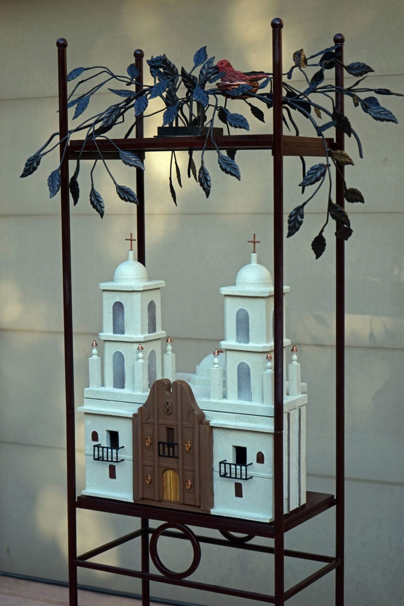 A metalwork sculpture of a mission style monastary with a loose nest of leaves and a bird perched atop a it's mtal fram housing