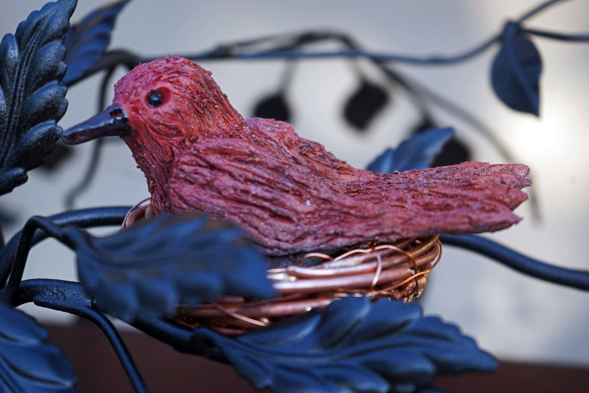 """a closeup shot of the intricate metalwork bird that sits atop the metal sculpture known as """"Mission"""""""